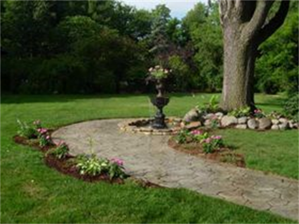 """Our funeral home is blessed with beautiful gardens located in the center of the block behind the funeral home. These are accessible through the gate in the picket fence from the large back parking areas. The gardens were designed by Laurel Pray to hold some of her favorite flowers which she often referred to as her """"old friends"""". The garden features a wide variety of flowers and brightly colored bushes, a water fountain with a cobblestone walk, a Tibetan Prayer Flag Garden, and room enough on th"""