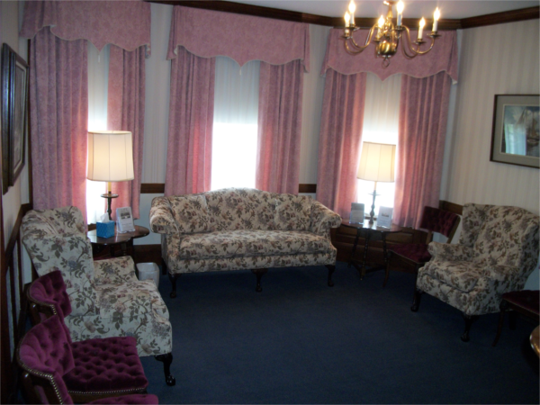 The middle sitting room is a place for individuals, groups and organizations to gather during a service or visitation.  It has cherry woodwork and a carved fireplace with a tile surround that is original to the house.