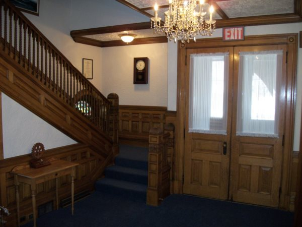 The front foyer features intricate white oak woodwork and a chandelier, both of which capture the character of the home.